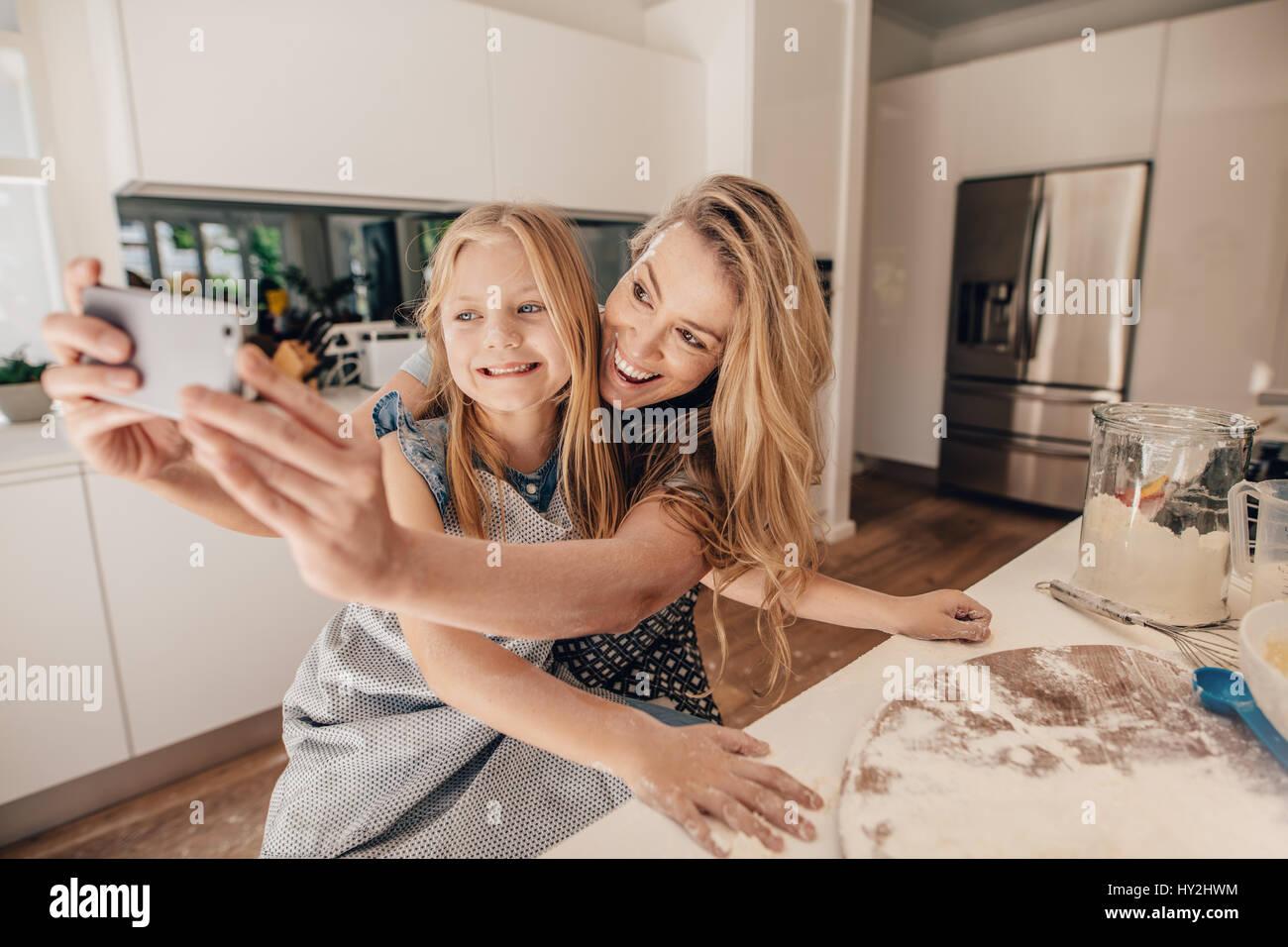Jolie petite fille et sa belle mère en souriant et selfies préparer la pâte pour la cuisson dans Photo Stock