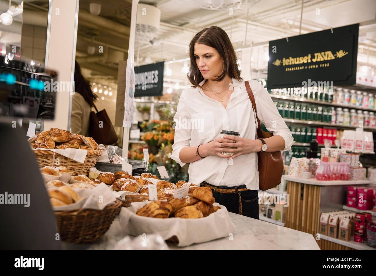 La Suède, femme choisissent des aliments dans une boulangerie Photo Stock