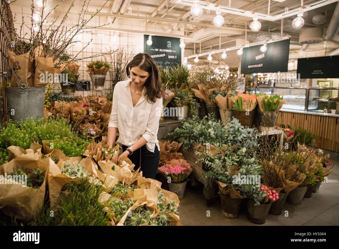La Suède, femme de choisir des fleurs en boutique Photo Stock