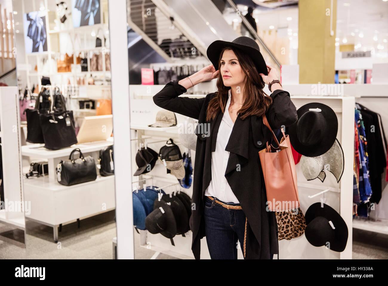 La Suède, femme choisissant hat in shop Photo Stock