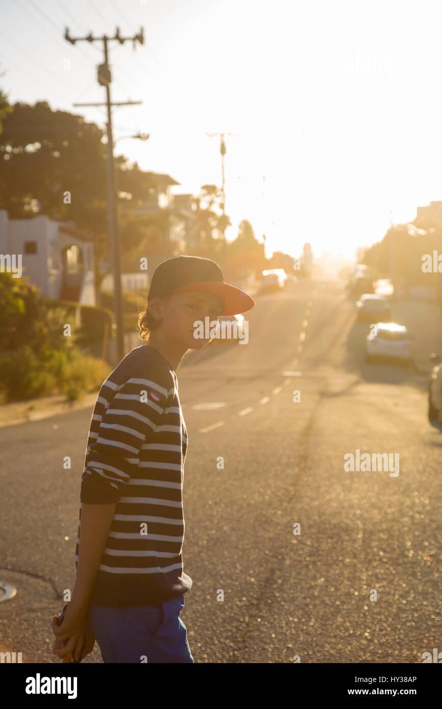 États-unis, Californie, Pacific Grove, boy (14-15) Comité permanent sur la route de banlieue Photo Stock