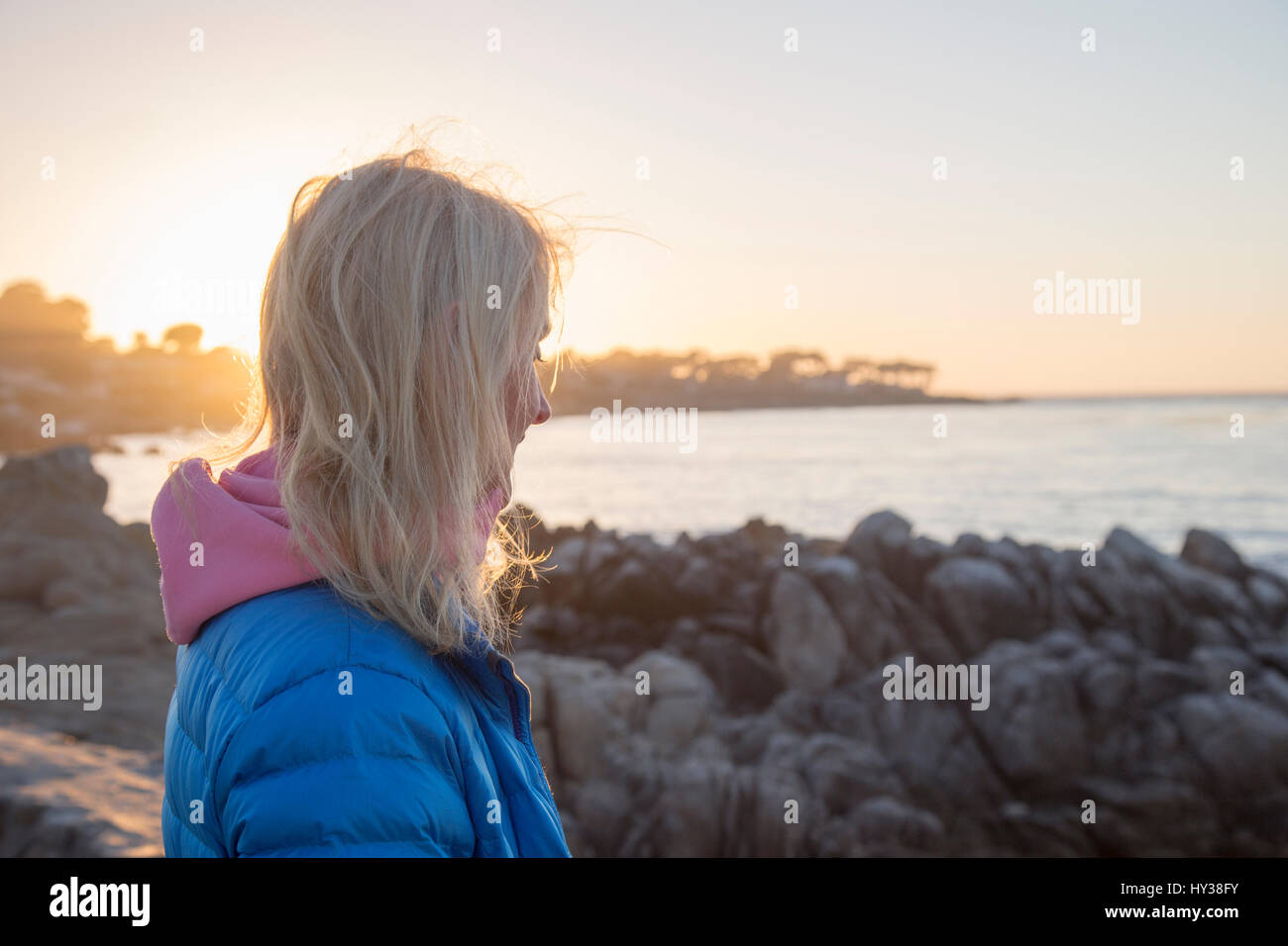 États-unis, Californie, Pacific Grove, young woman on rocky seashore au coucher du soleil Photo Stock