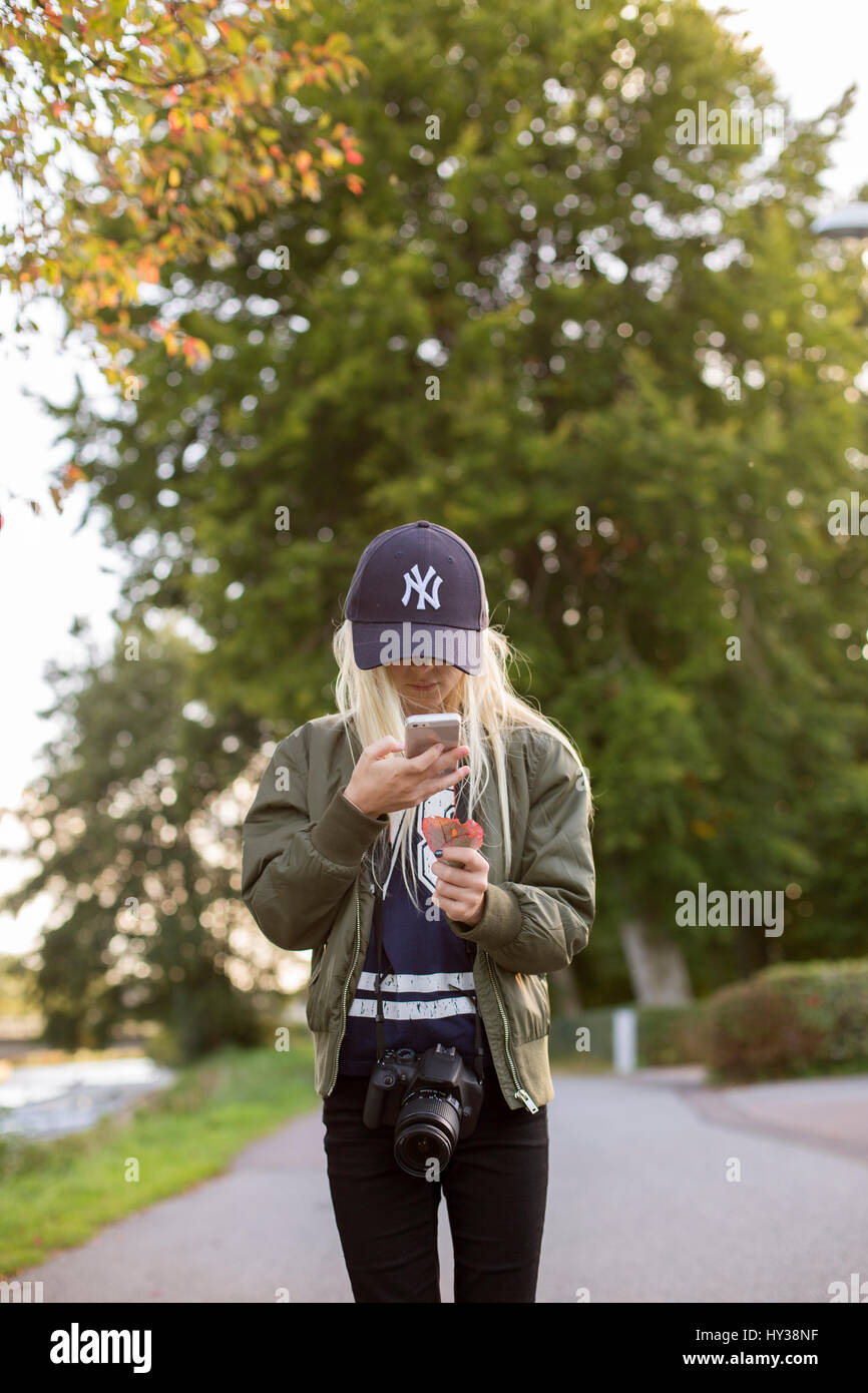 La Suède, girl (12-13) photographier avec des feuilles cell phone Photo Stock