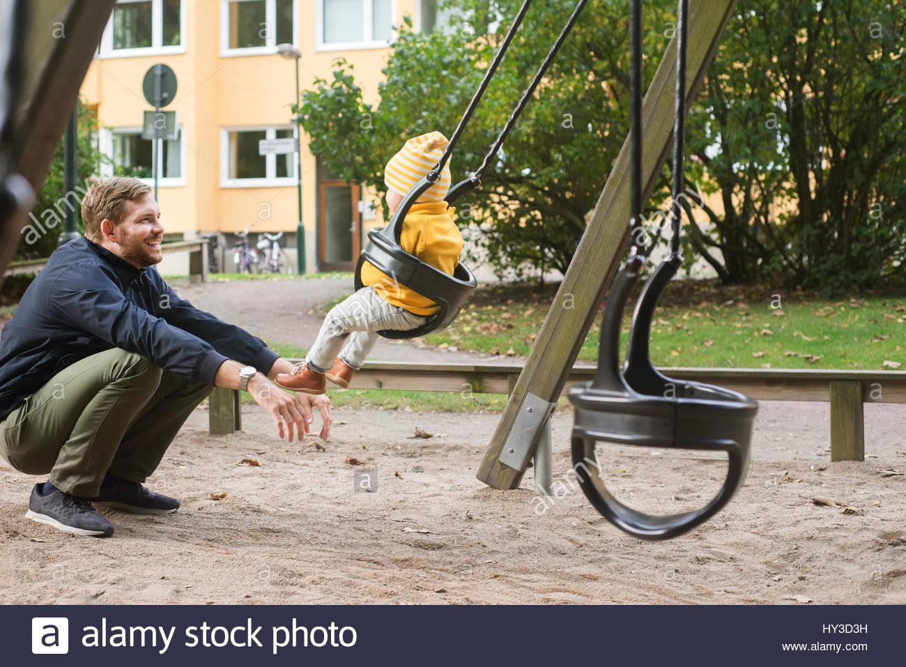 La Suède, Stockholm, Malmö, père fils oscillante ( 12-17 mois) en jeu pour enfants Photo Stock