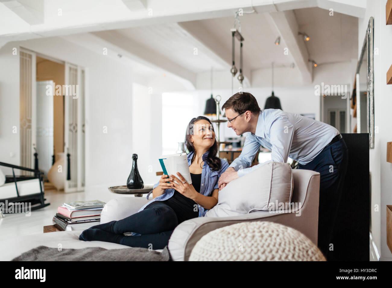 Allemagne, femme assise sur un canapé et souriant à l'homme Photo Stock