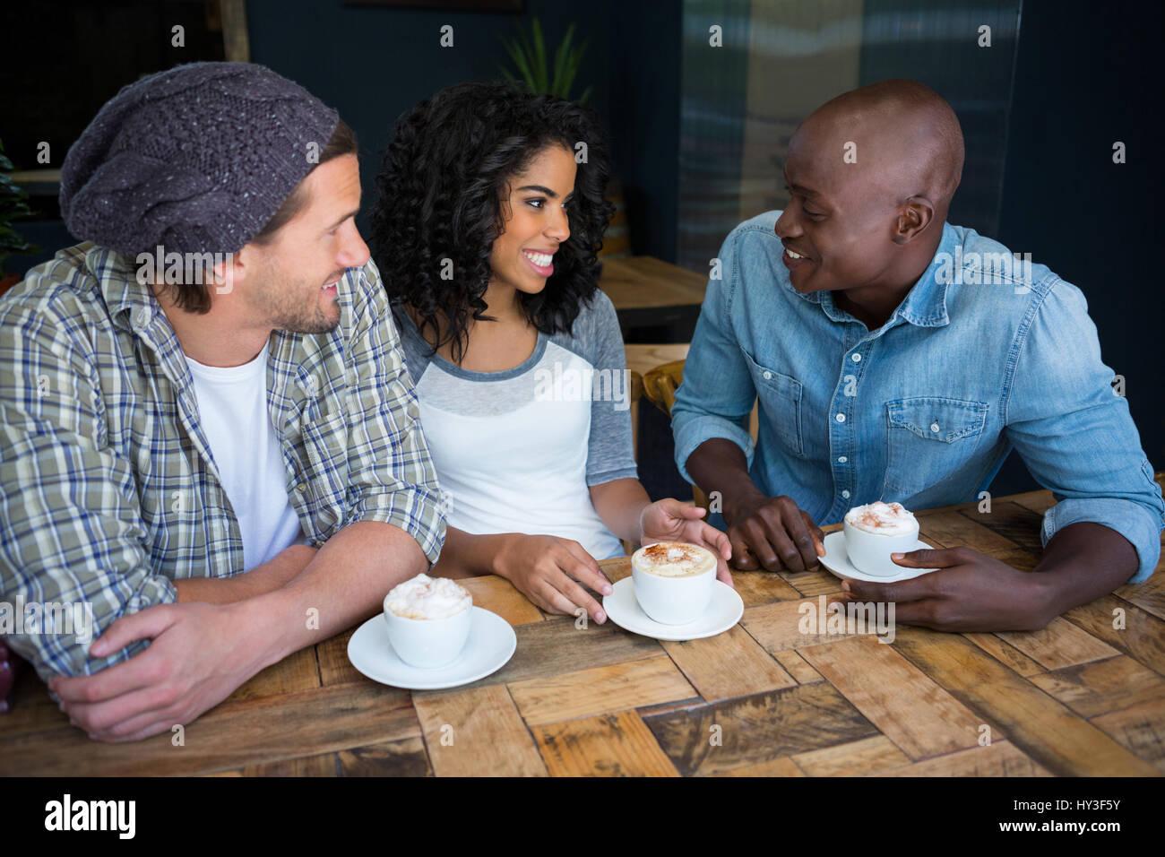 Multi Ethnic amis parler tandis que le café à table in coffee shop Photo Stock