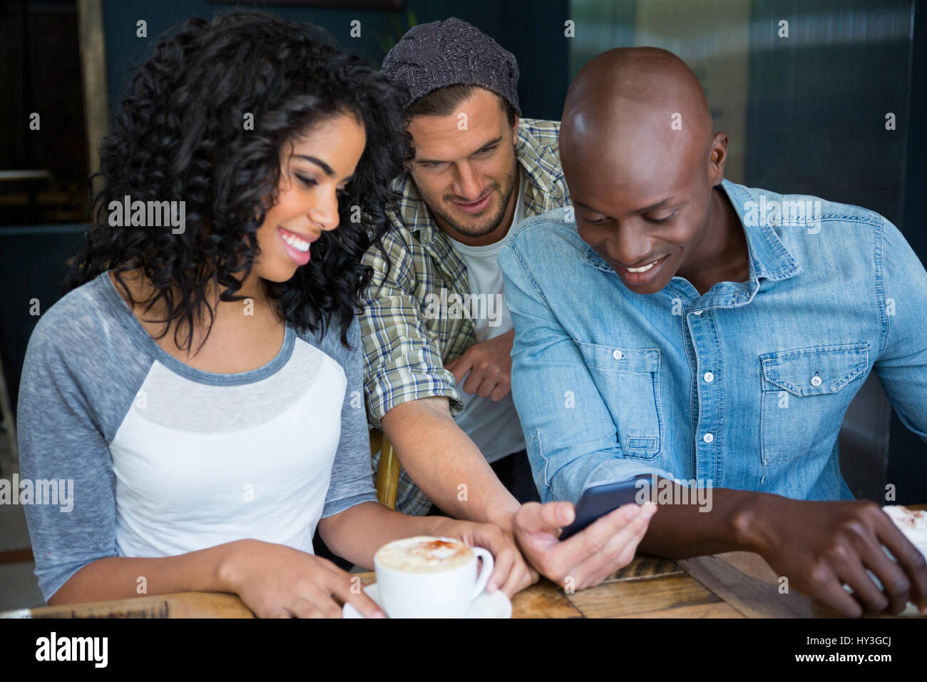Mâle et femelle multi ethnic friends using mobile phone in coffee shop Photo Stock