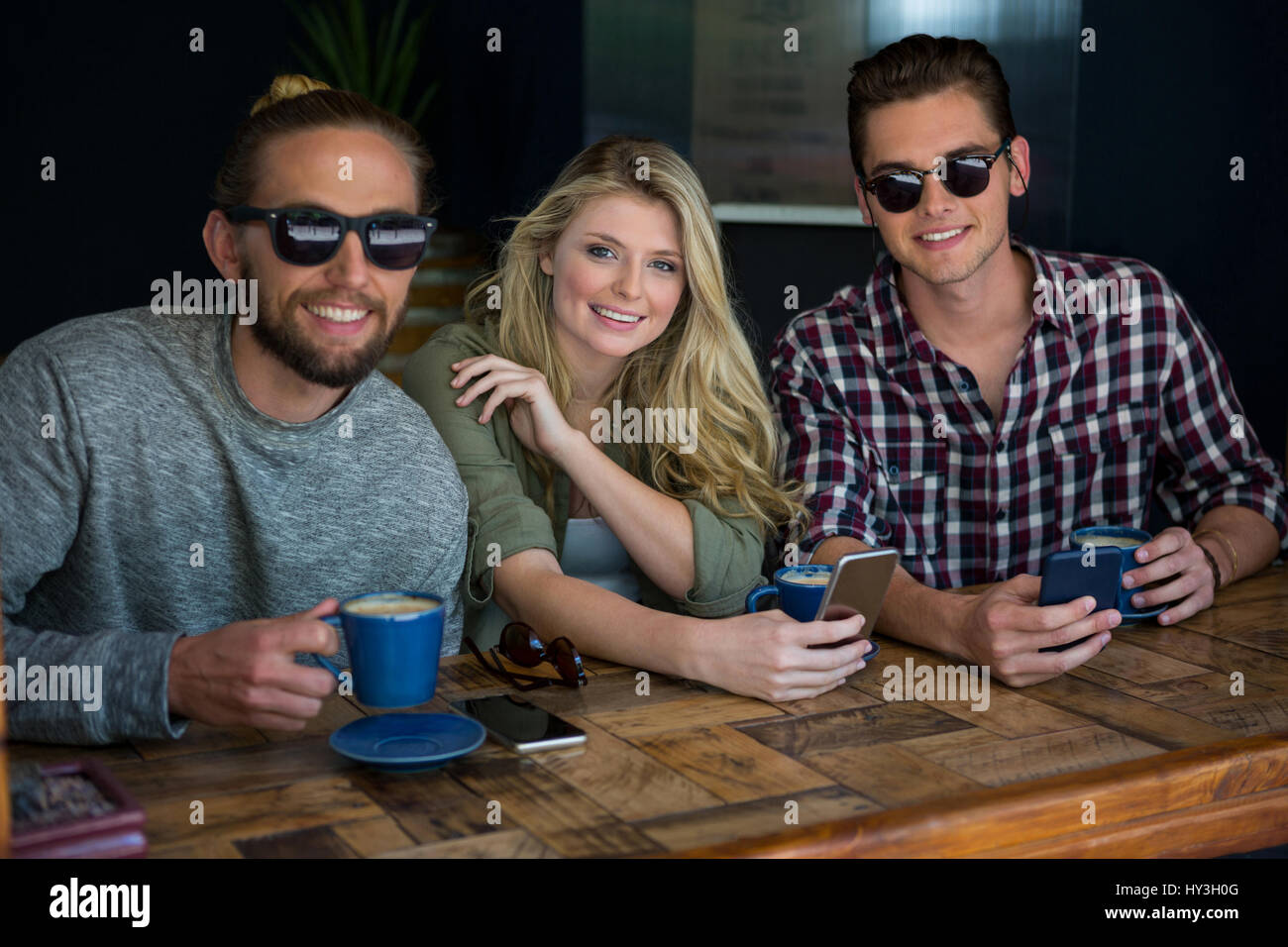Portrait de femme avec des amis masculins portant des lunettes de soleil in coffee shop Photo Stock