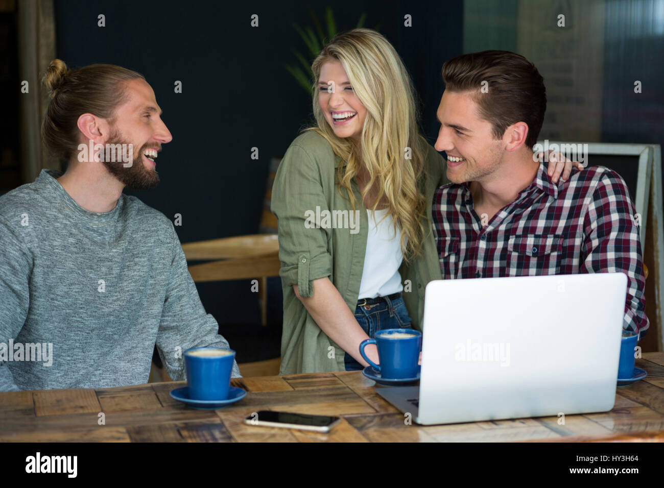 Mâle et femelle Cheerful young friends talking in coffee shop Photo Stock