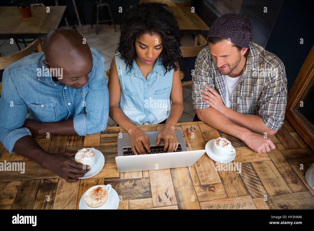 Portrait d'amis à l'aide d'ordinateur portable à la table en bois dans la région de coffee Photo Stock