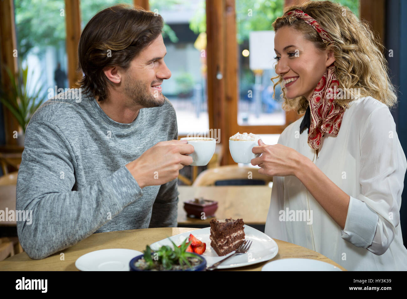 Smiling young couple having coffee at table in cafeteria Banque D'Images