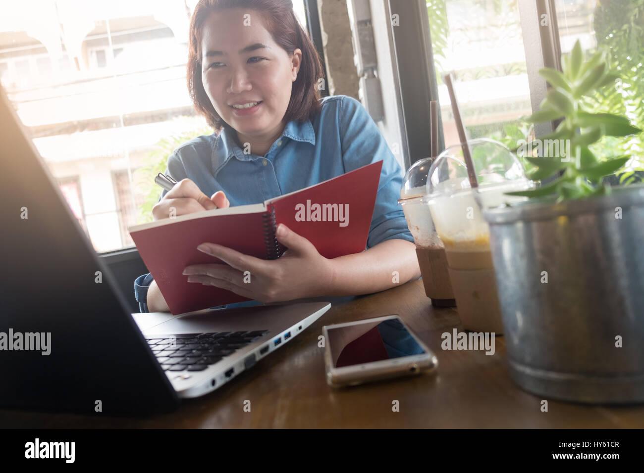 Young Asian woman writing hipster sur le portable tout en travaillant avec un ordinateur portable dans un café. Photo Stock