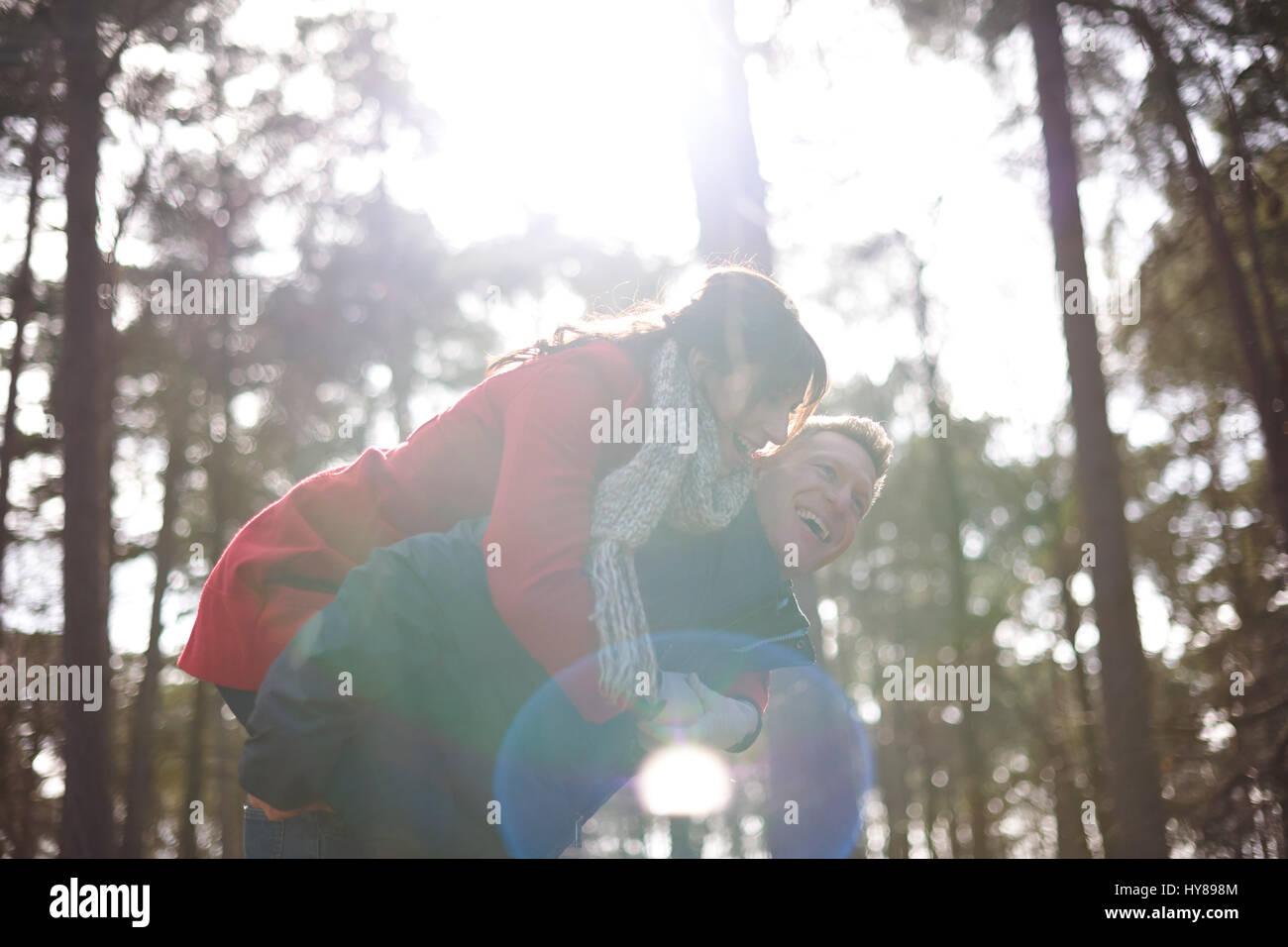 Un homme donne sa partenaire féminine un piggy back sur une promenade n les bois Photo Stock
