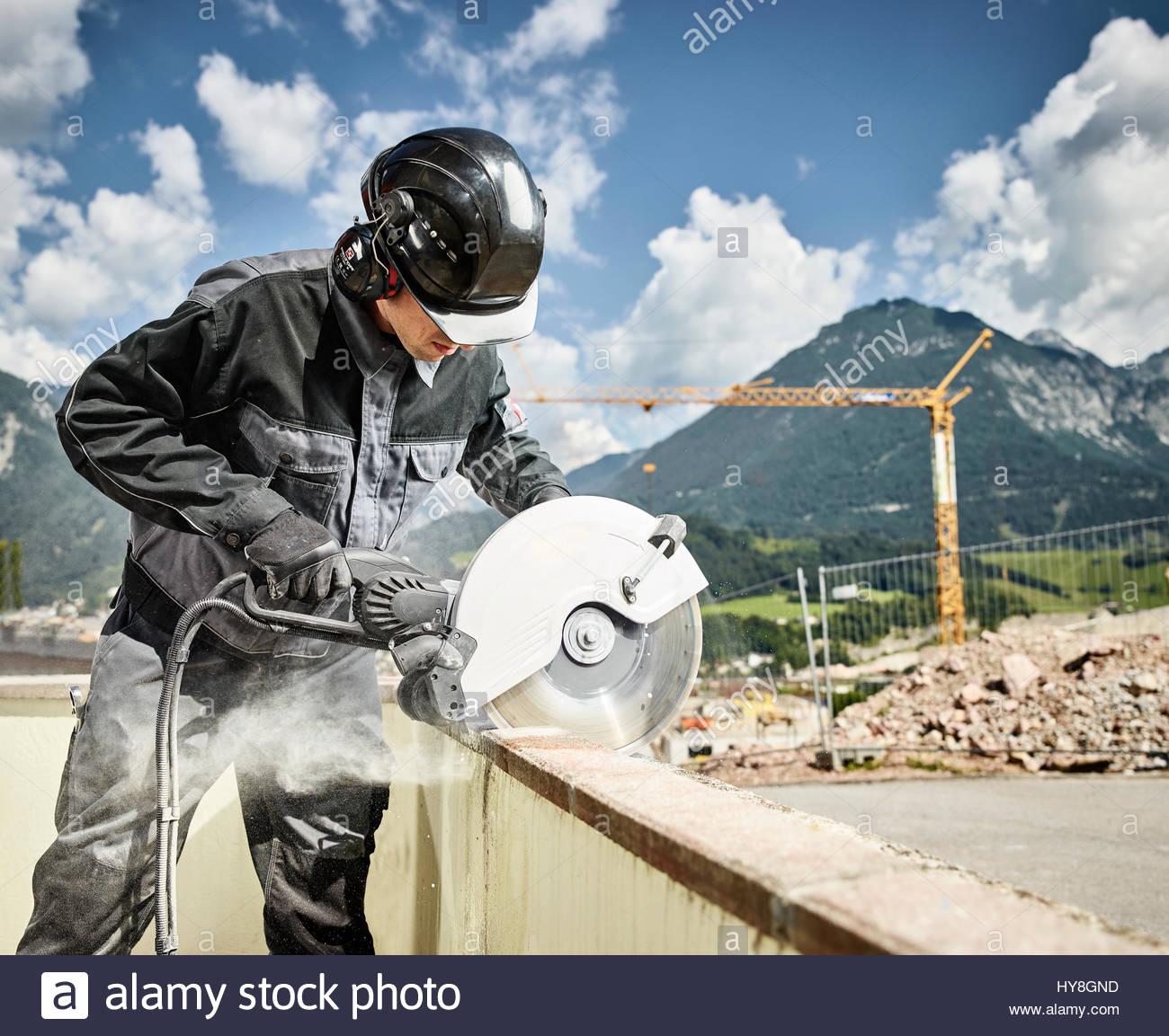 Travailleur de la Construction avec casque, vêtement de travail et protection auditive mur de béton coupe Photo Stock
