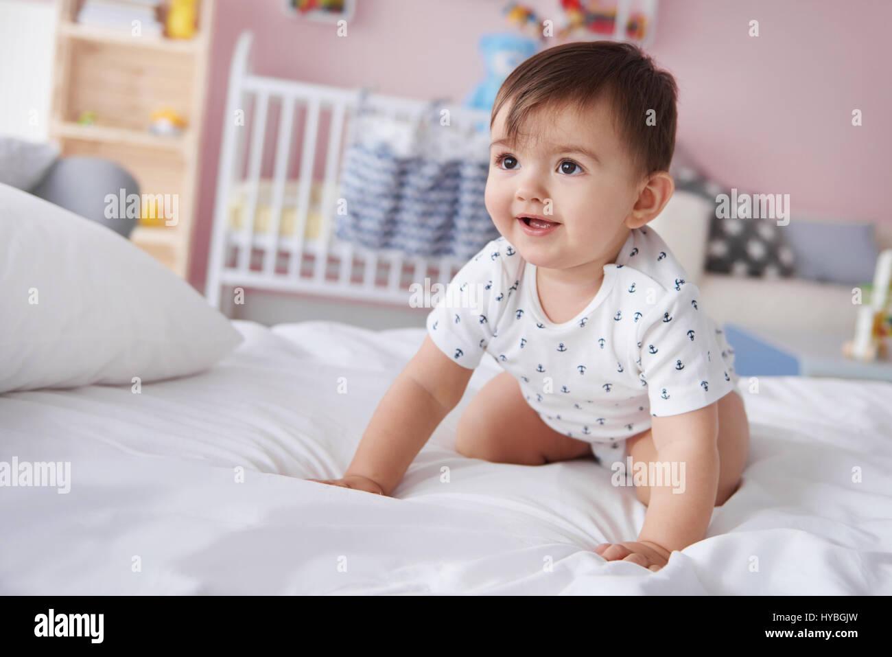 Smiling baby boy de ramper sur le lit Photo Stock