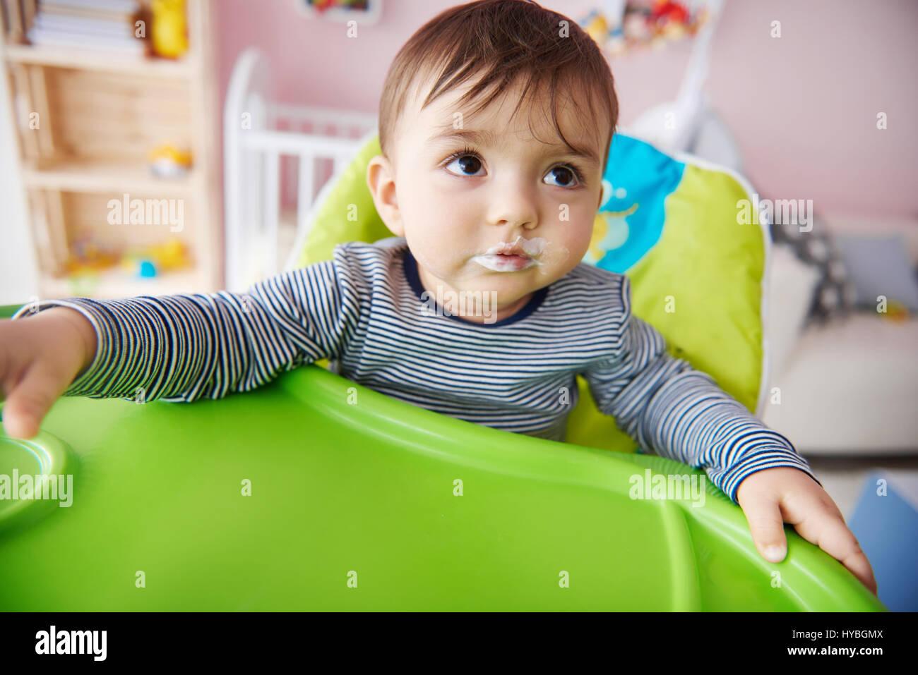 Close up of petit garçon assis sur la chaise haute Photo Stock