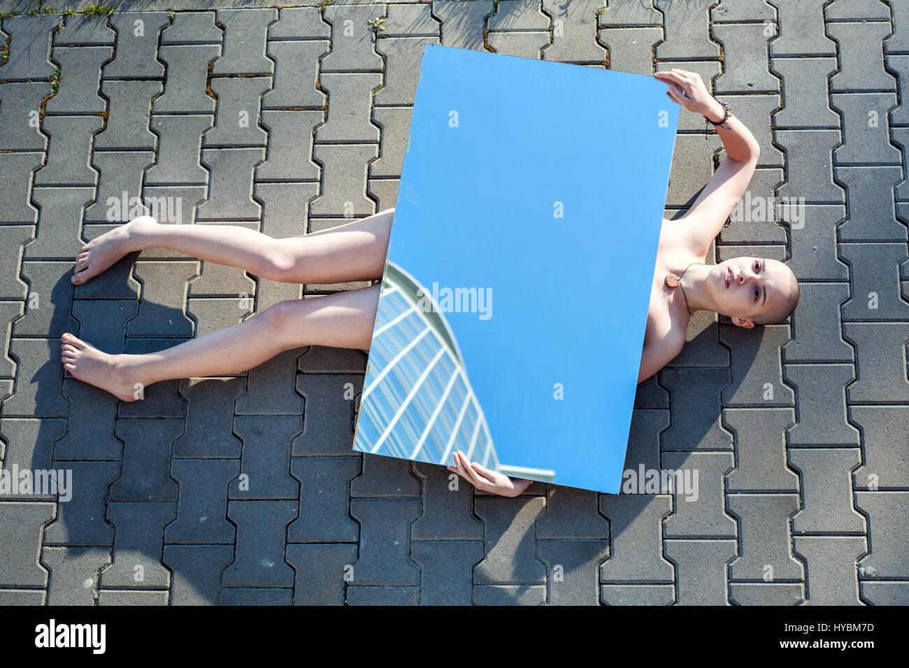 Étrange jeune femme couchée sur la route sans aucun signe de vie. Photo Stock
