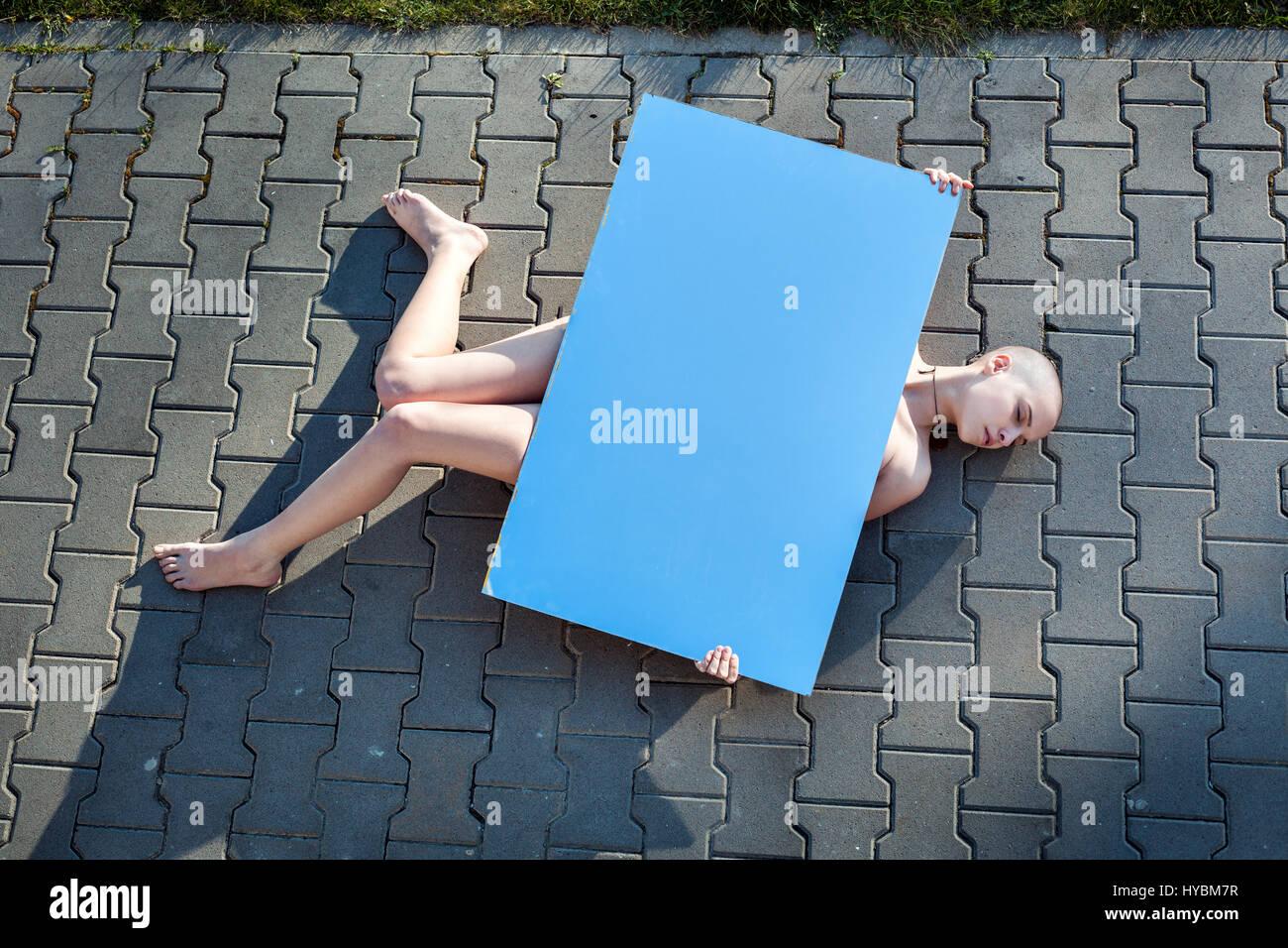 Femme allongée sur le trottoir sans aucun signe de vie. Photo Stock
