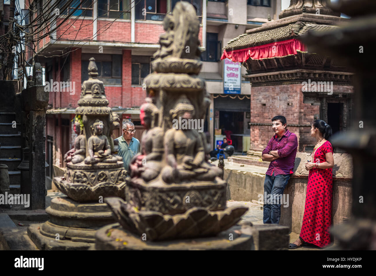 La population locale ayant le temps de loisirs près de sculptures hindoues au quartier résidentiel de Photo Stock