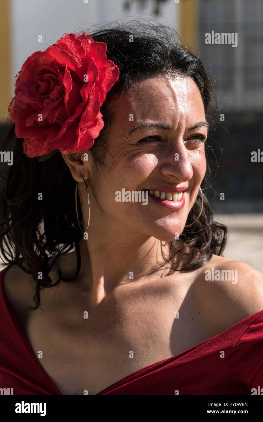 Une espagnole vêtue comme une danseuse de flamenco portant une rose rouge dans ses cheveux dans l'attente d'une Banque D'Images