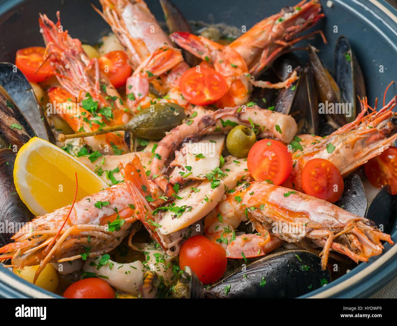 Des fruits de mer colorés avec des légumes et épices sur plaque bleue en restaurant. Close up Banque D'Images