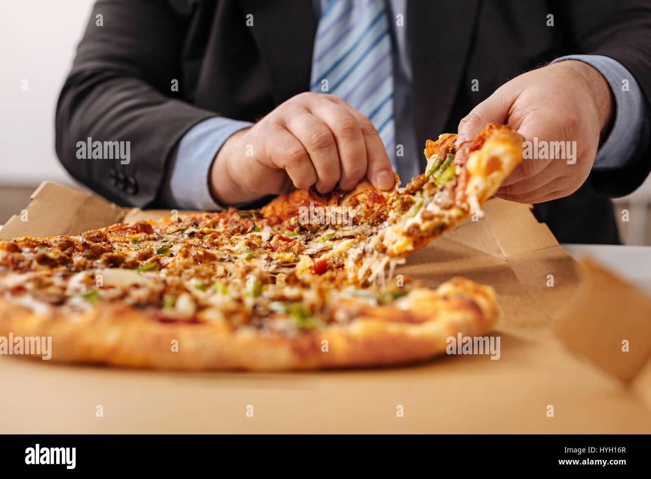 Employé de la compagnie de première ligne eating pizza Photo Stock