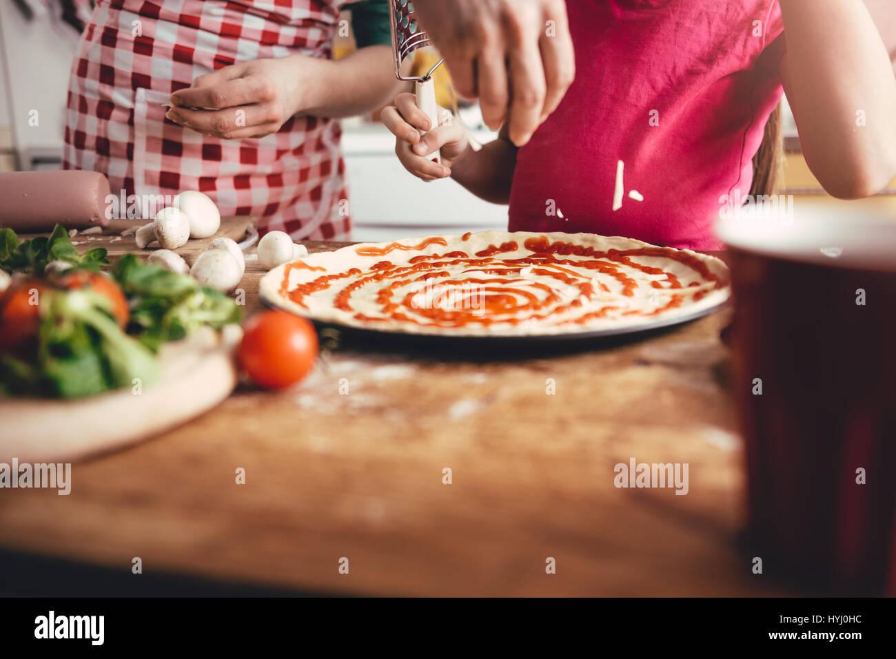 Mère et fille la préparation de pizza dans la cuisine Banque D'Images