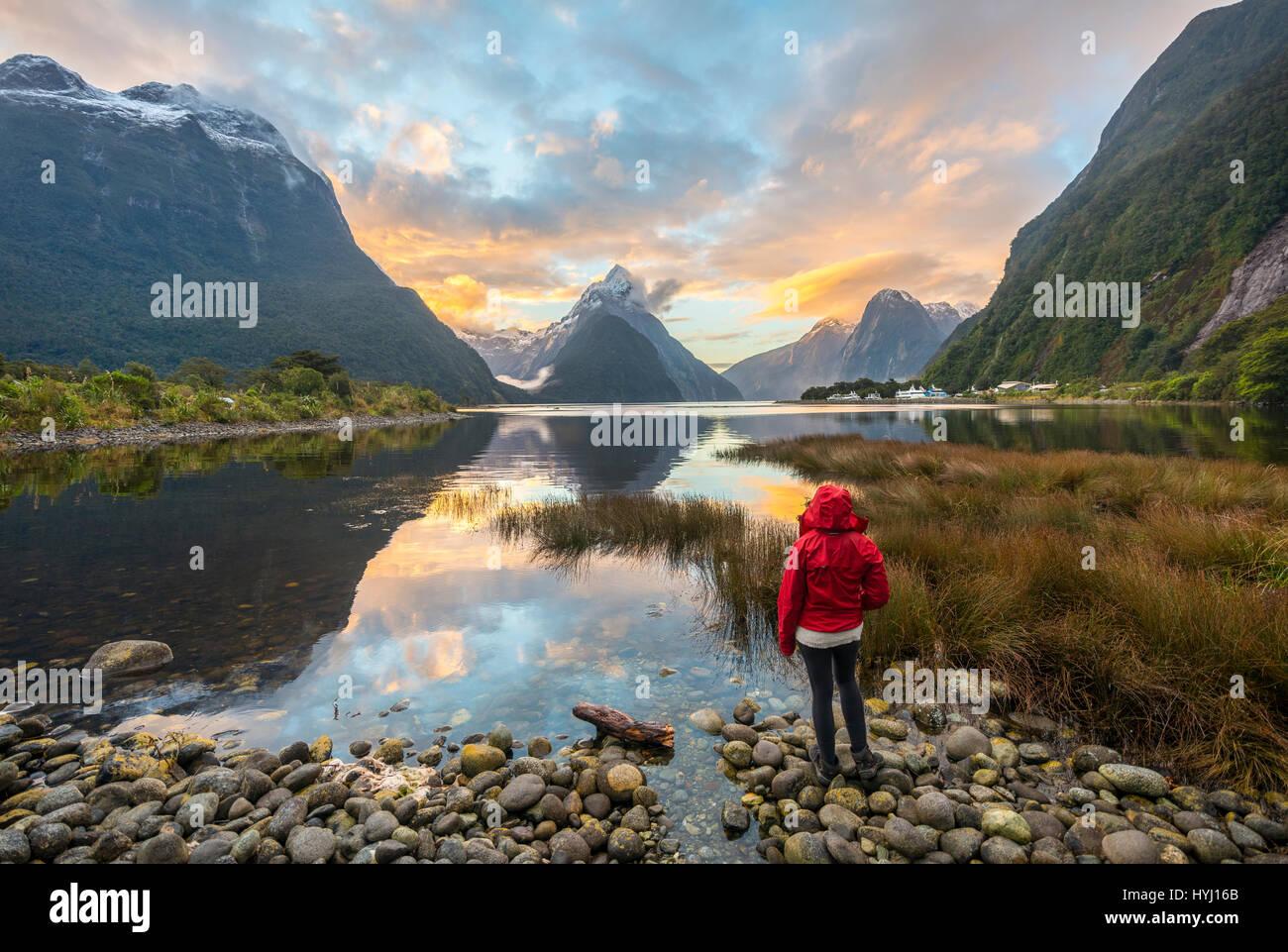 Les touristes à la recherche sur le paysage, la Mitre Peak reflète dans l'eau, coucher de soleil, Photo Stock