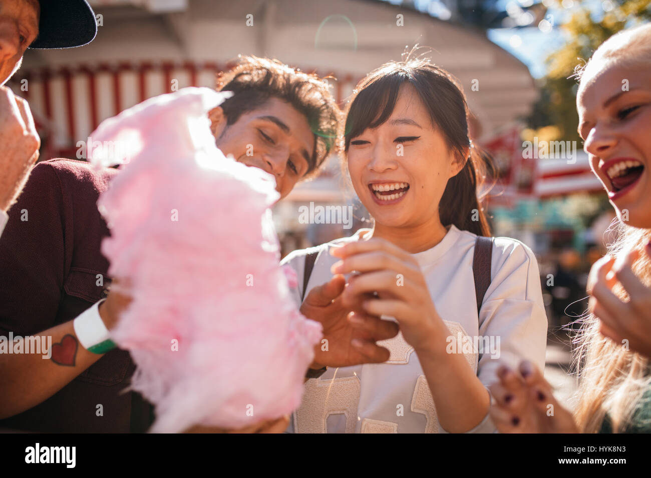 Groupe d'amis manger candyfloss au parc d'amusement. Smiling young personnes partageant la barbe à Photo Stock