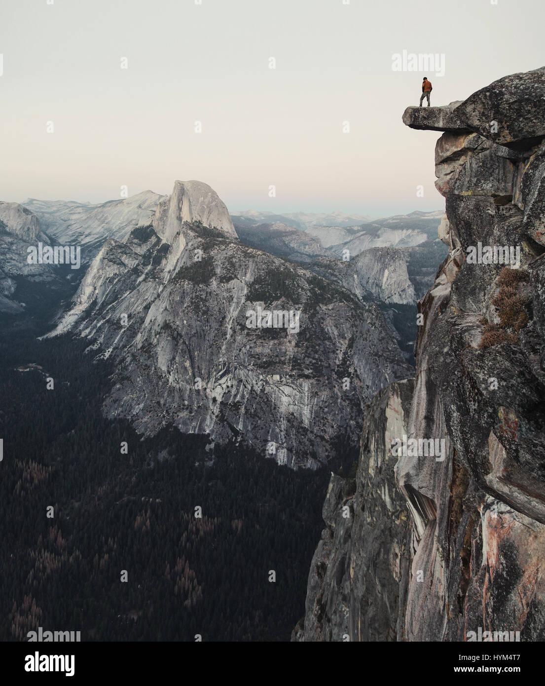 L'intrépide randonneur est debout sur un rocher en surplomb en profitant de la vue vers célèbre Demi Dôme à Glacier Point in Yosemite National Park, Californie Banque D'Images
