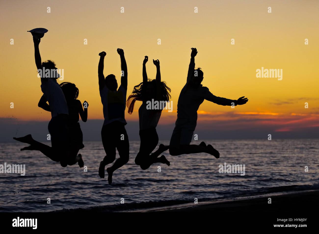 Silhouette d'amis sautant sur plage, pendant l'heure du coucher du soleil Photo Stock