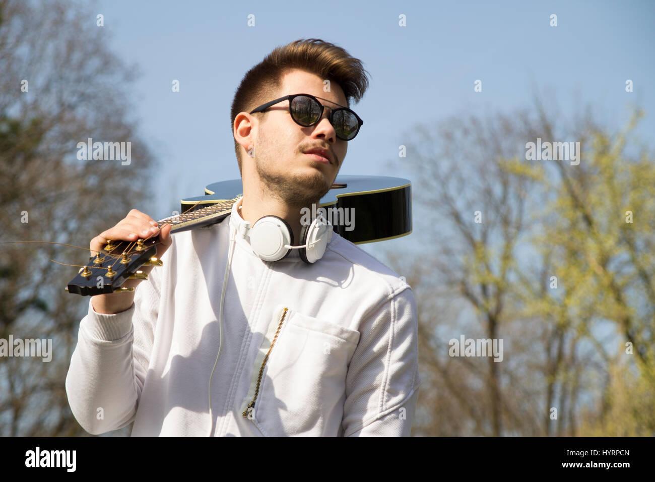 Beau jeune homme, profitant du parc avec une guitare.focus sélectif et petite profondeur de champ. Photo Stock
