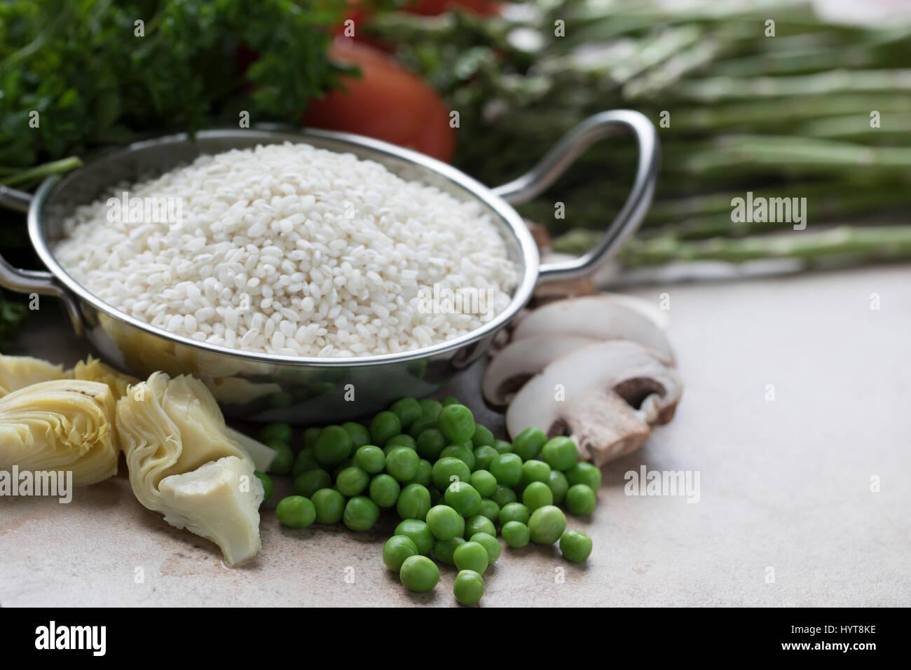 Le riz, artichauts, petits pois, champignons et autres ingrédients pour la paella végétarienne Photo Stock
