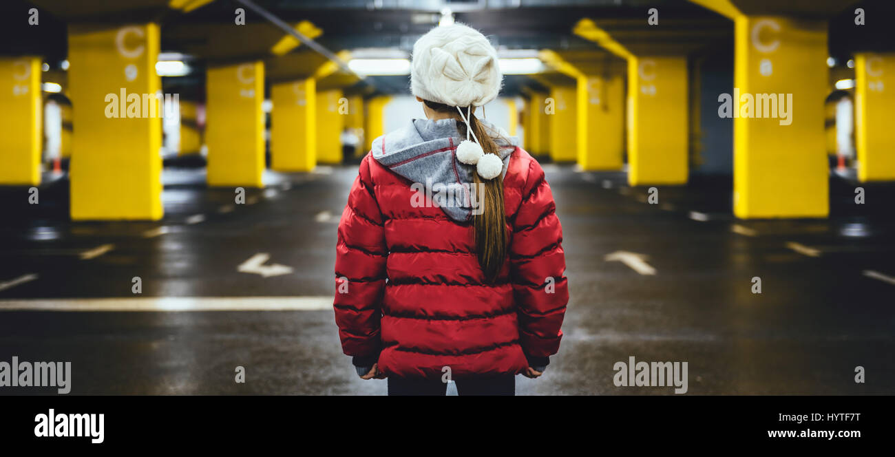 Girl wearing white hat et red jacket debout dans le parking public garage Photo Stock