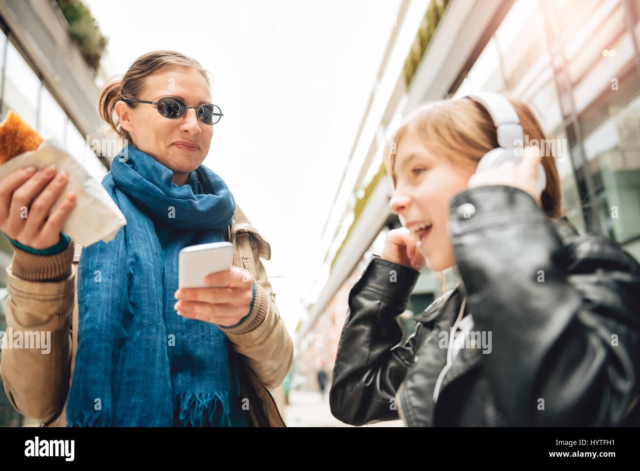 L'écoute de la musique sur le casque fille avec mère debout à côté et manger Photo Stock