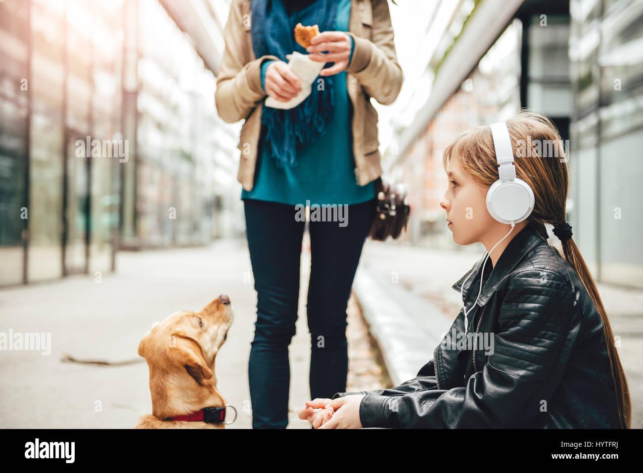 L'écoute de la musique sur le casque fille tandis que la mère et son chien debout à côté Photo Stock