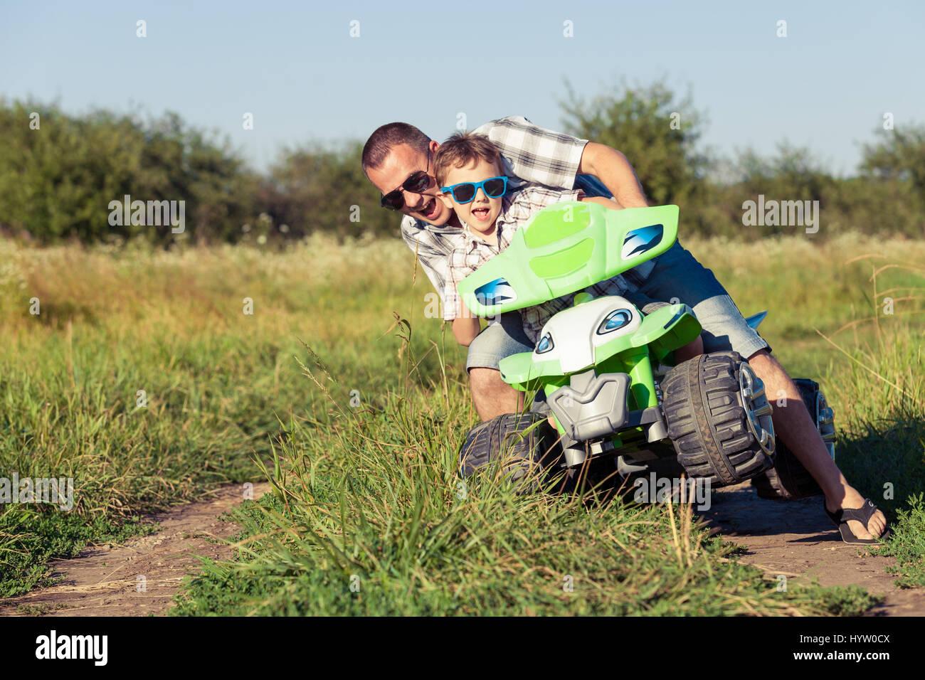 Père et fils jouant sur la route, à la journée. Ils la conduite sur quad dans le parc. Les gens s'amusant sur la Banque D'Images