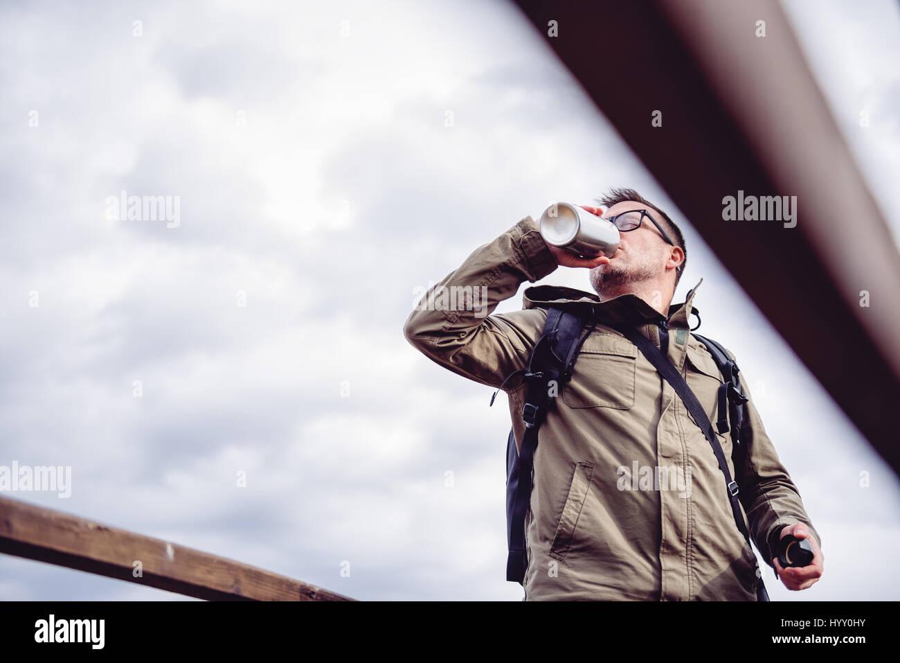 Hiker resting on clôture en bois et l'eau potable Photo Stock