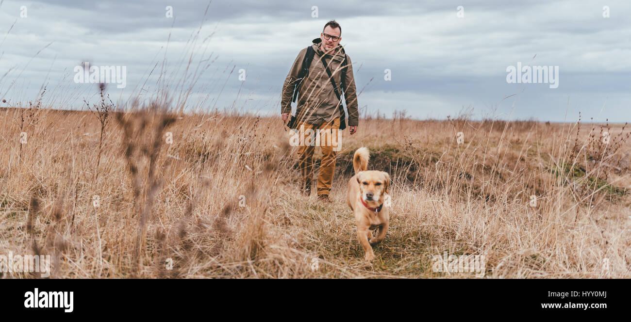 Randonneur et petite promenade de chien jaune dans l'herbage dans un jour nuageux Photo Stock