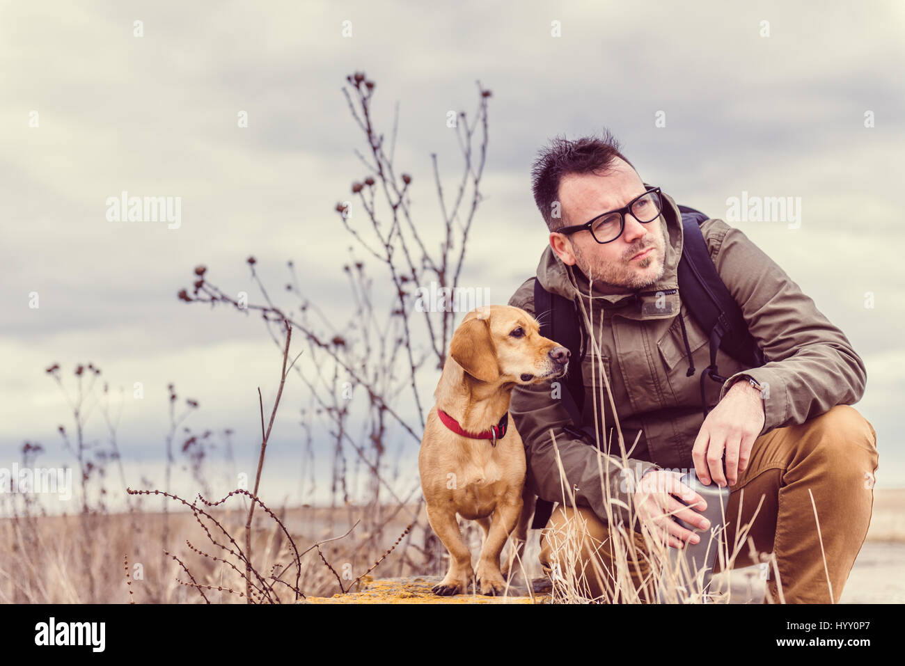 Randonneur et chien reposant sur l'ancien mur de briques Photo Stock