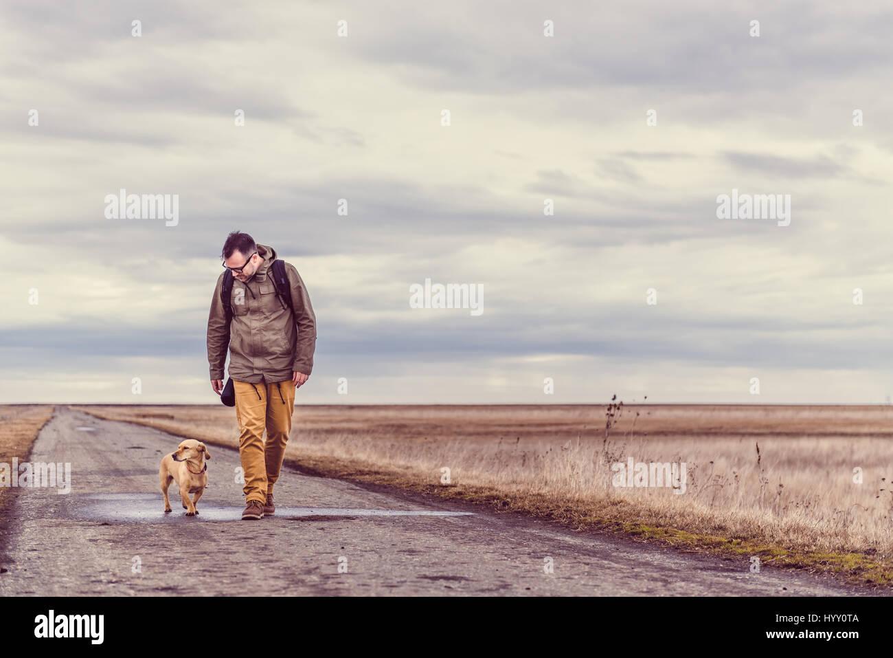 Randonneur et promener le chien sur une route sur un jour nuageux Photo Stock