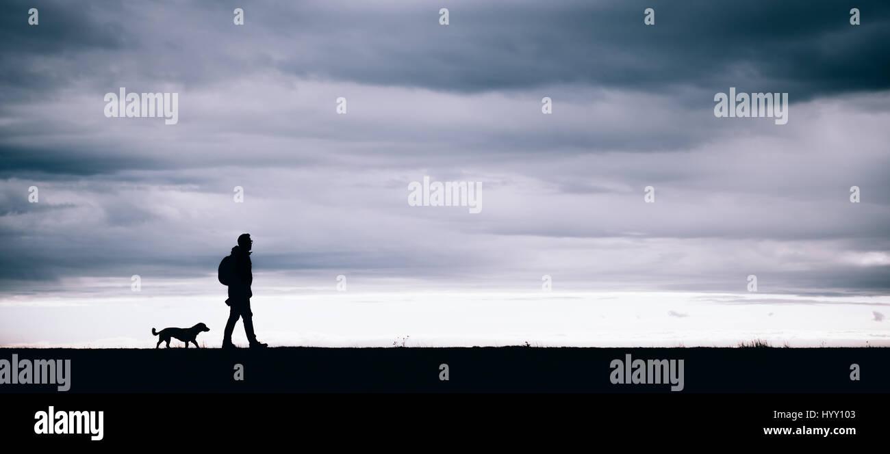 Silhouette de randonneur et de chien à marcher ensemble Photo Stock
