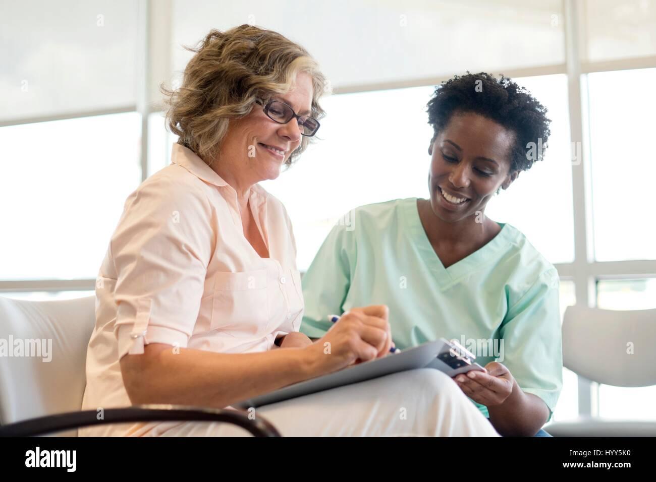 Femme mature de remplir le formulaire avec une infirmière, souriante. Photo Stock