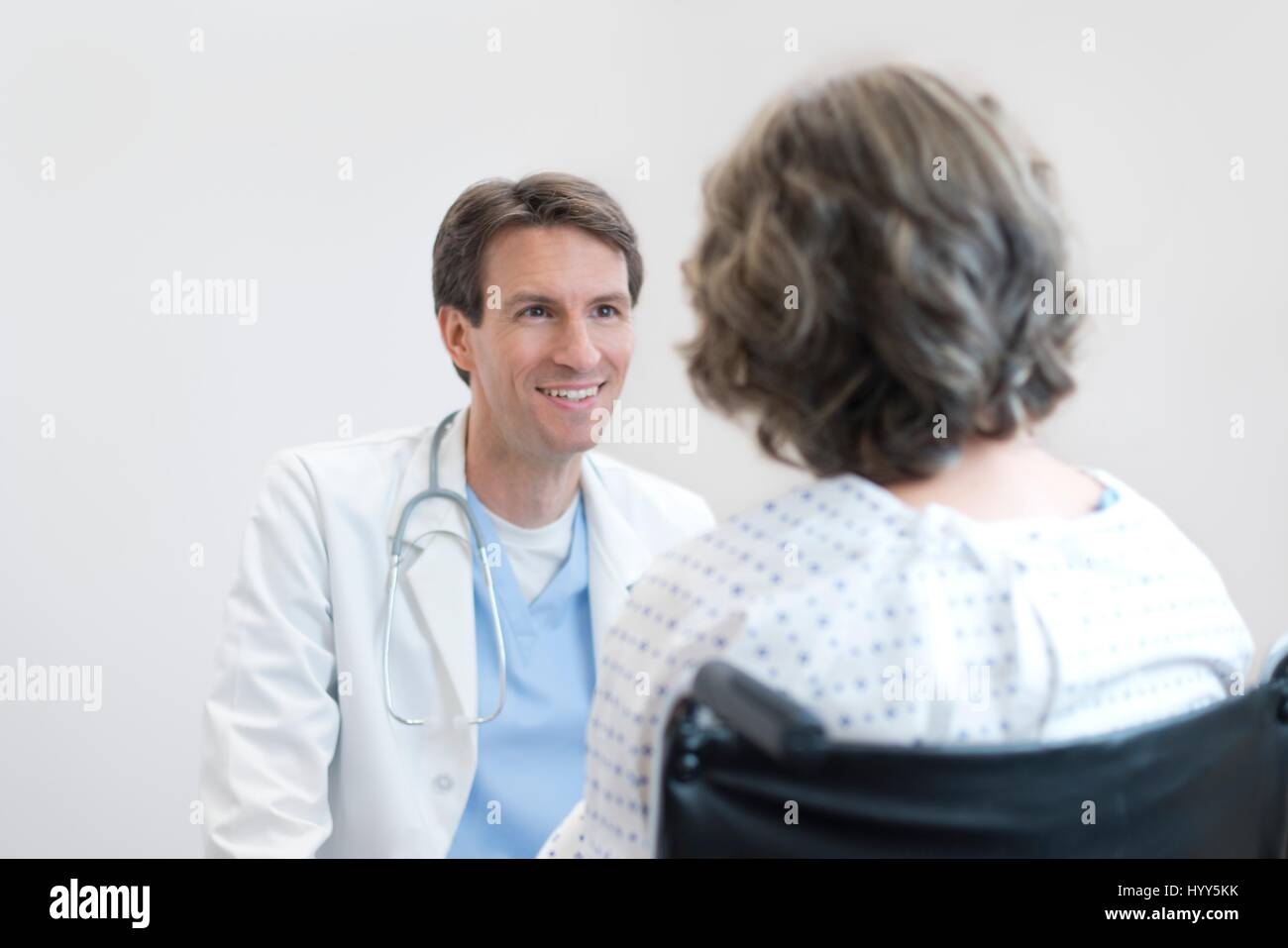 Doctor smiling at mature female patient in wheelchair. Photo Stock