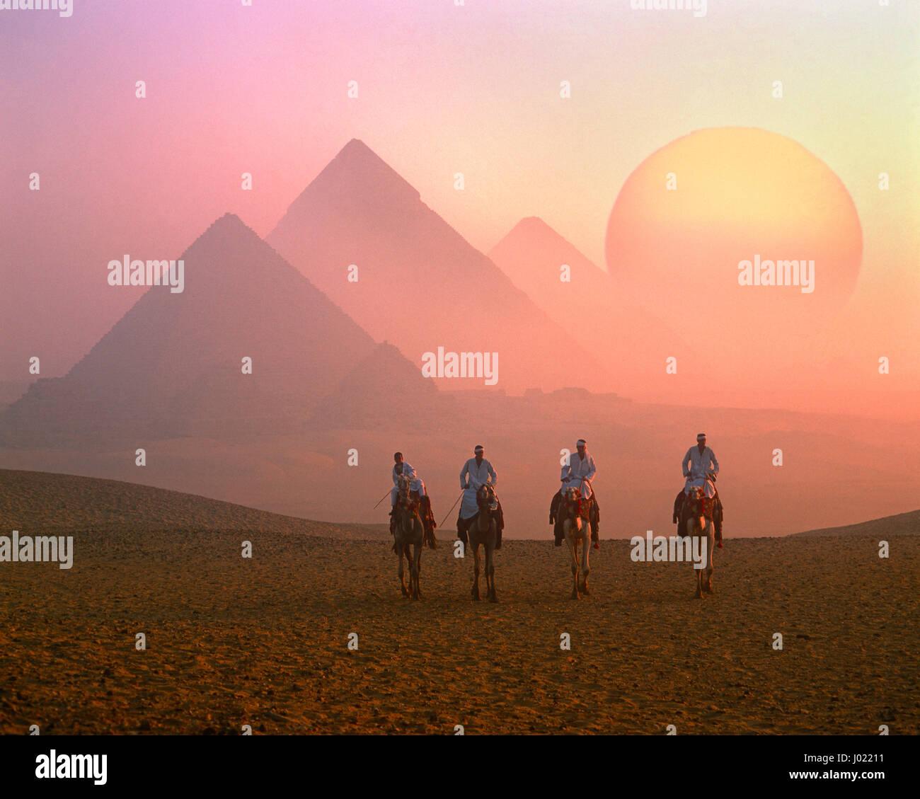 Quatre coureurs de chameau, les Pyramides et le soleil levant, Giza, Le Caire, Egypte Photo Stock