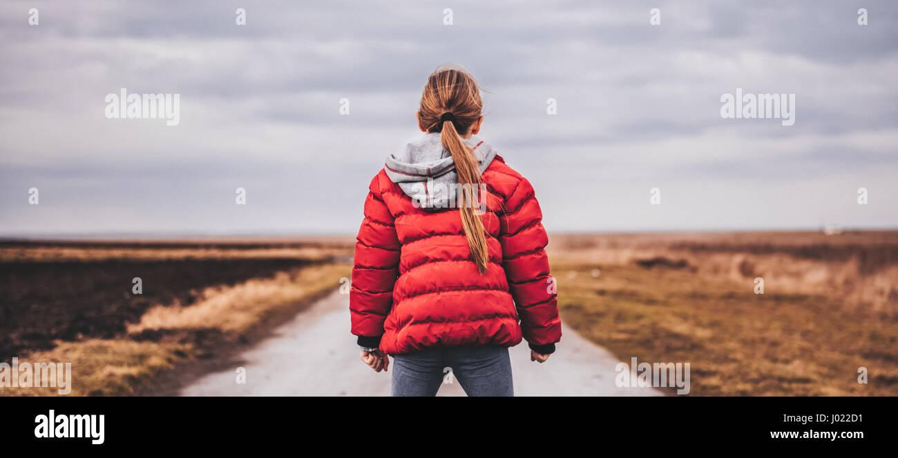 Girl wearing red jacket debout seul sur la route et à la recherche à distance Photo Stock