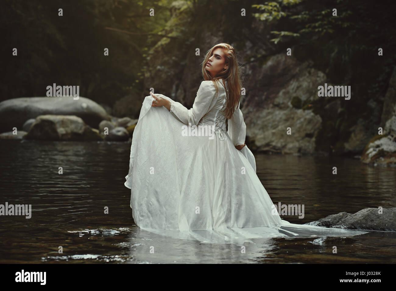 Belle femme éthérée dans les eaux mystiques. Étang de fantaisie Photo Stock