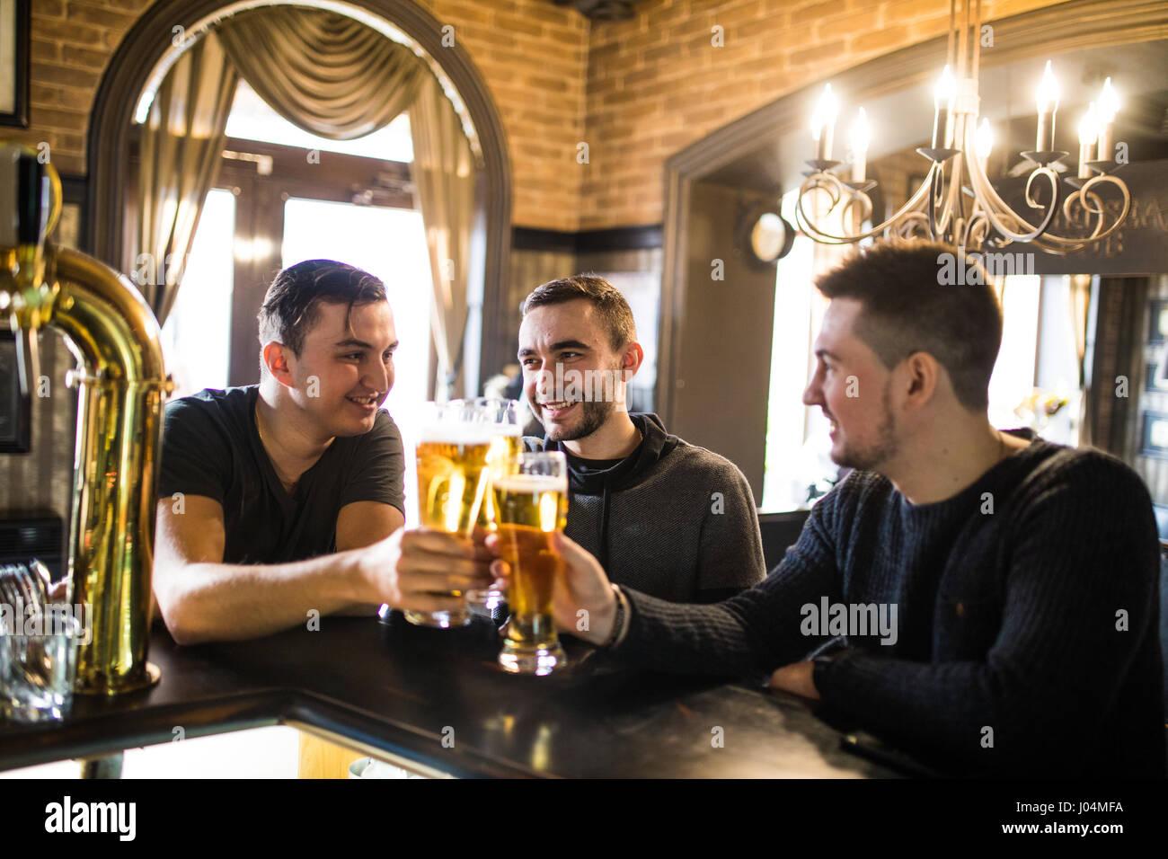 Cheerful vieux amis s'amuser et de boire la bière au comptoir du bar dans un pub. Photo Stock