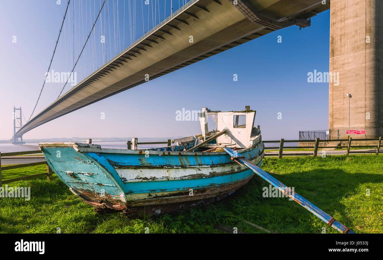 L'abandon d'un bateau en bois sous le Humber Bridge qui enjambe l'estuaire de la Humber et visualisés Photo Stock