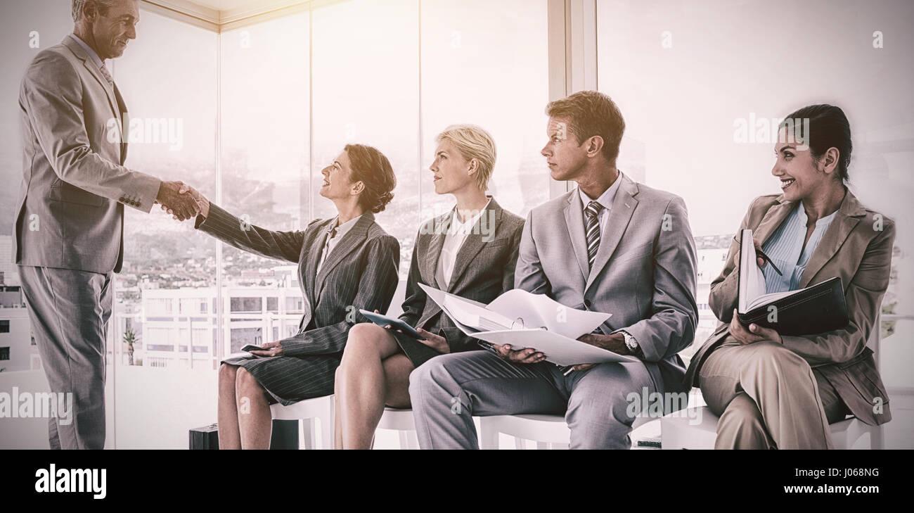 Accueillir des gens d'affaires en attente d'interview in office Photo Stock